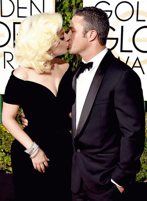 Lady Gaga and Taylor Kinney attend the Golden Globes and kiss for the camera on the red carpet.