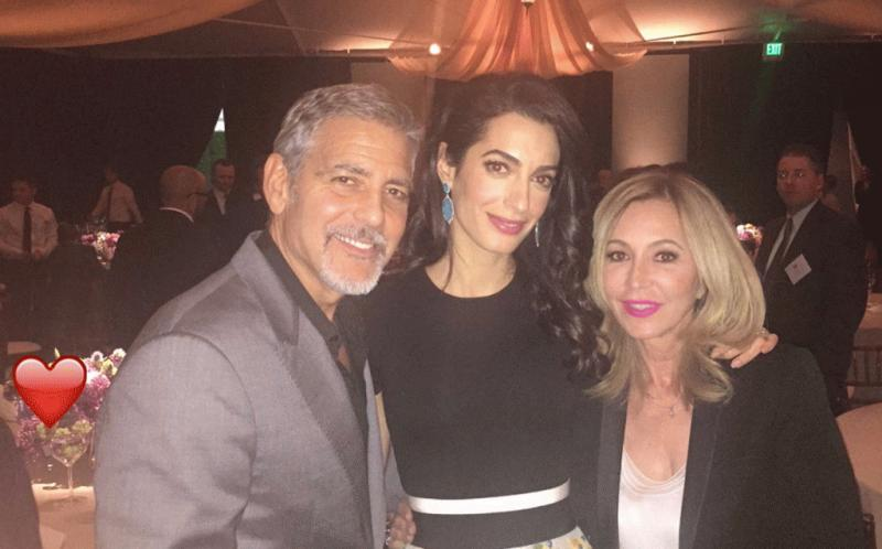 George and Amal Clooney at the fundraiser for Hillary Clinton, which they hosted, pose for a photo with Anastasia Soare, the founder of the beauty brand Anastasia Beverly Hills.
