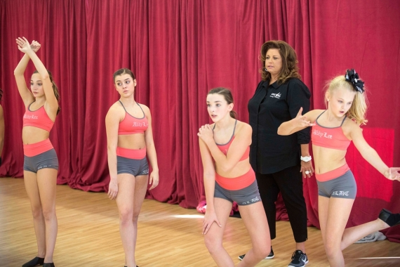 "A still showing Abby Lee Miller with her dancers in one of the episodes of ""Dance Moms."""